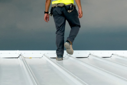 Roofing contractor walking metal roof