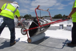 Spreading silicone roof coating on flat roof