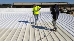 Roofing contractor spraying acrylic roof coating on metal roof