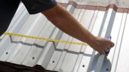 Worker showing how to measure metal roof profile