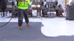 Roofer spraying silicone coatings on a flat roof