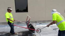Roofing contractors applying urethane roof coatings with tank spreader
