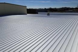Highly-reflective acrylic roof coatings on metal roof