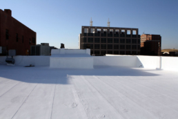 Acrylic roof coatings on a modified bitumen roof