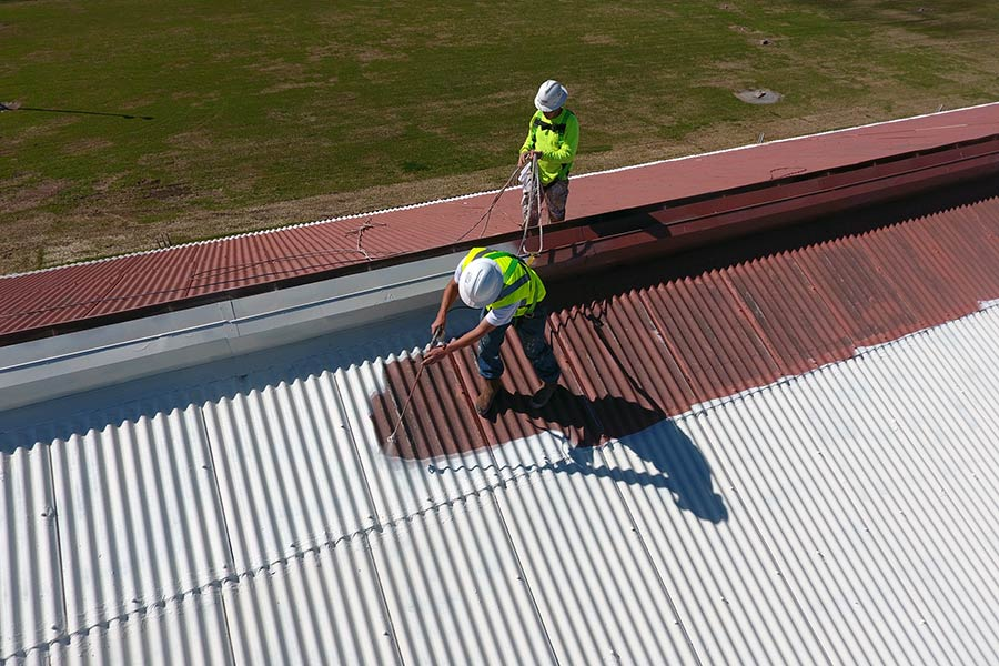 Roofers applying an acrylic roof coating to large metal roof
