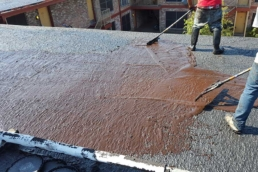 Roofers applying asphalt emulsion on built-up roof
