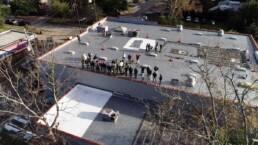 Roofing professionals on a flat roof at FAST Academy
