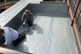 Roofers applying urethane roof coating on rooftop
