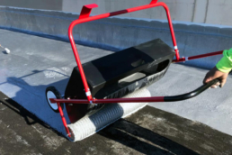 Roofer appying urethane roof coating with tank spreader