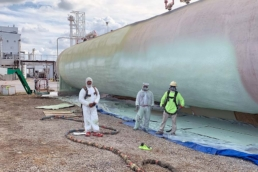 Workers posing in front of large carbon dioxide storage tank