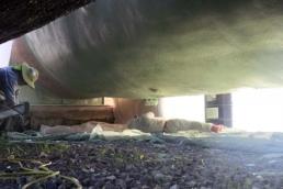 Worker applying butyl coating under steel storage tank