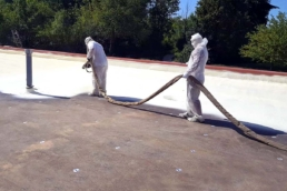 Roofers applying spray polyurethane foam and roof coating system to flat roof