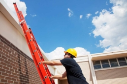 Commercial roofing contractor climbing ladder to access roof