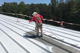 Roofer spraying acrylic roof coating on leaky metal roof