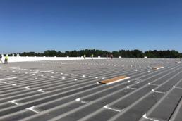 Roofing contractors applying Met-A-Gard System to leak metal roof