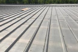 Leaky metal roof being prepared for roof coatings