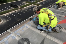 Roofing contractor waterproofing fasteners with urethane mastic