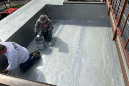 Roofers applying base coat of Aromatic Urethane 520 to details