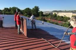 Roofers spray applying silicone base coat to metal roof