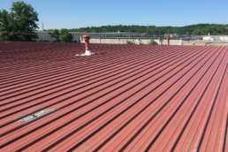 Metal roof with red-colored primer