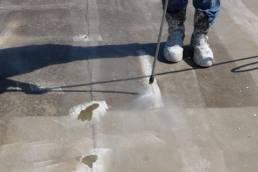 Roofer pressure washing silicone-coated modified bitumen roof