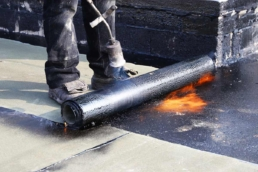 Roofer torch-applying bitumen to roof