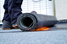 Rolls of modified bitumen material being torch-applied to roof surface