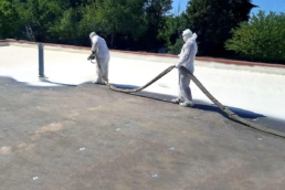 Roofing contractors installing spray foam system of flat roof