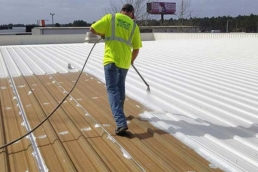 Roofing contractor spray applying acrylic base coat during metal roof restoration