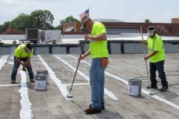 Roofers coating seam of flat roof with thick waterproofing mastic