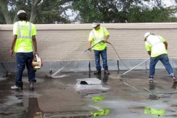 Roofing contractors pressure washing flat roof surface