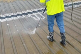 Roofer pressure washing metal roof surface
