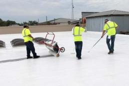 Top coat application of flat roof restoration