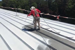 Roofer spraying acrylic coating on metal roof