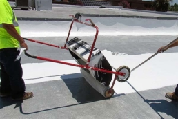 Roofing contractors applying silicone coating with a tank spreader