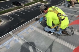 Commercial roofer applying roof mastic over metal roof fasteners