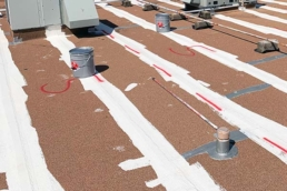 Silicone roof mastic on the seams of a commercial flat roof