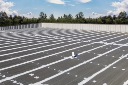 Silicone roof mastic on seams of commercial metal roof