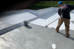 Roofing contractor applying silicone top coat to fast food industry roof