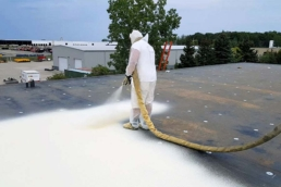 Roofing contractor applying SPF roofing system on commercial flat roof