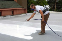 Commercial roofer applying elastomeric coating to spray foam roofing system