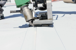 Commercial roofing contractor re-roofing with single-ply roofing membrane