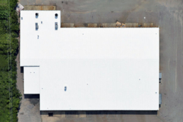 Bright-white commercial metal roof after coating application