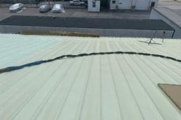 Spray polyurethane foam layer over metal roof